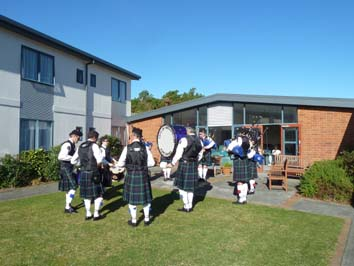 In the courtyard, in the Sunshine, playing well known Scottish tunes.